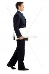 Business man portrait walking with his laptopisolated over a white background