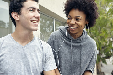 Young couple listening to music together with earphones