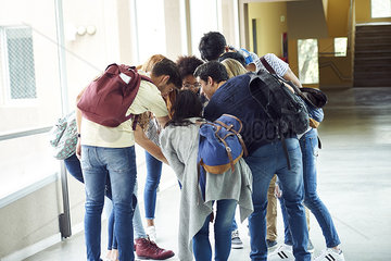 Group of students bending forward in a circle together in school corridor