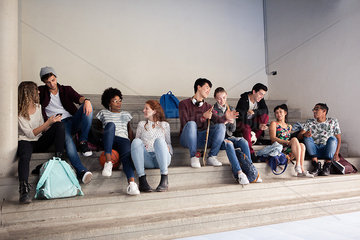 Group of students hanging out and chatting on stairs