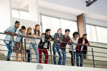 Group of students standing together on mezzanine  watching event