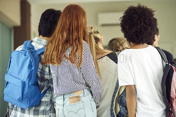 Students standing in school corridor  rear view