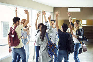 Group of students standing in circle in corridor with hands raised in the air