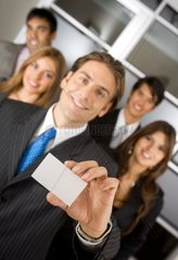 businessman showing his business card with a group behind