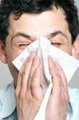 Mann niest in ein Taschentuch
