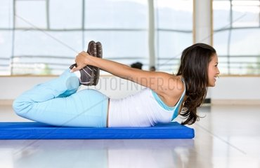 Woman stretching her torso at the gym