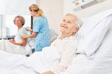 Seniorin im Krankenbett im Pflegeheim