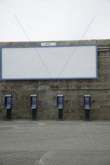 Vier Telefonzellen unter leerem Plakat