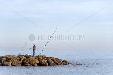 Pietra Ligure  Italien  ein Angler steht auf einer Mole