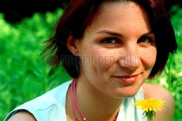 Berlin  eine junge Frau mit Loewenzahn