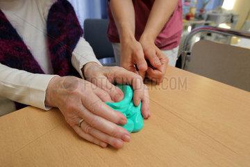 Flensburg  Deutschland  Ergotherapeutin macht mit einer Patientin Uebungen mit Knetgummi