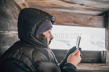 Austria  Kitzbuehel  young woman in raised hide looking at cell phone in winter