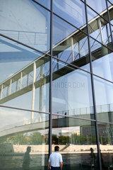 Berlin  Deutschland  Spiegelung der Fussgaengerbruecke in der Paul-Loebe-Hausfassade