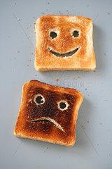 Zwei Scheiben Toastbrot - eine mit einem laechelnden Gesicht  die andere mit einem traurigen