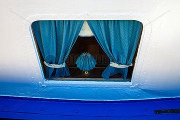 Luke mit blauen Gardinen im Rumpf eines Schiffs