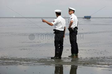 Cuxhaven  Deutschland  Polizisten stehen in Gummistiefeln im Watt