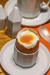 Fruehstuecksei in einem Eierbecher mit weichem Dotter