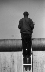 Mann steht auf einer Leiter schaut ueber die Berliner Mauer