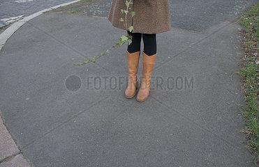 Frau mit Stiefeln wartet auf dem Gehweg