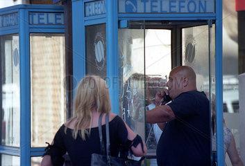 Mann telefoniert in einer Telefonzelle der Romtelecom SA  Bukarest