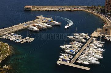 Weisse Motorjacht faehrt in den Yachthafen Fontvielle am Mittelmeer