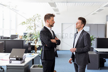 Two businessmen standing in office  discussing solutions
