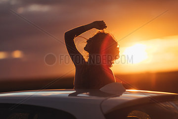 Woman outside the car at sunset  raised arm