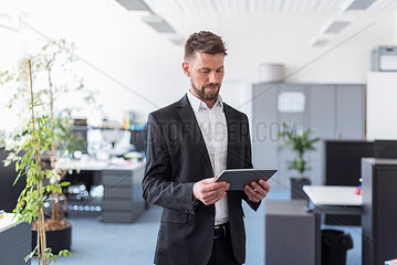 Successful businessman standing in office  using digital tablet
