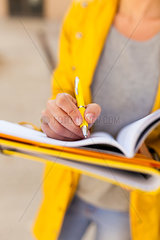 Close-up of woman taking notes outdoors