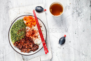 Vegan teriyaki bowl with pulled teriyaki beef made from jackfruit  spinach  rice and carrots