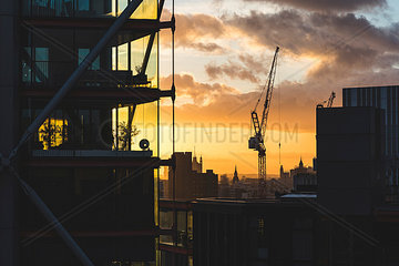 UK  London  buildings and crane silhouette at sunset with Big Ben and Westminster in far background
