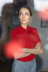 Portrait of woman wearing red blouse standing behind windowpane