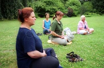 Frauen meditieren in einem Park in Berlin