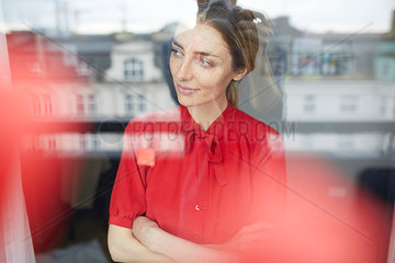 Portrait of smiling woman behind windowpane wearing red blouse