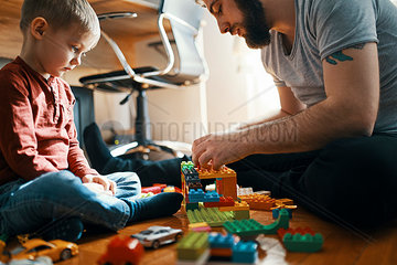 Father playing with building bricks on the floor while his sad little son watching him