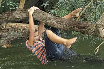 Maedchen klettert an Baum