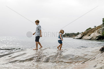 Greece  Chalkidiki  brother and little sister playing together on the beach