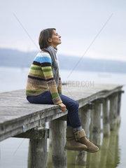 Frau sitzt auf einem Steg am See