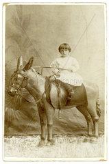 Kleines Maedchen auf hoelzernem Esel