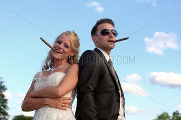 Berlin  Deutschland  ein Brautpaar posiert mit Zigarre