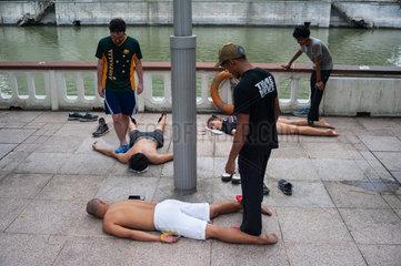 Singapur  Republik Singapur  Parkourlaeufer werden am Ufer des Singapore River massiert