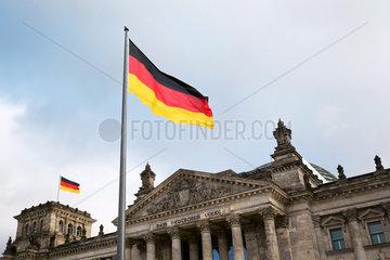 Berlin  Deutschland - Nationalfahne der Bundesrepublik Deutschland vor dem Reichstagsgebaeude.