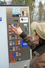 Eine junge Frau holt Zigaretten am Zigarettenautomat