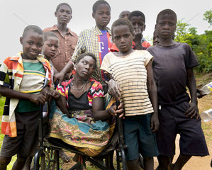 Junge Frau im Rollstuhl umringt von Freunden