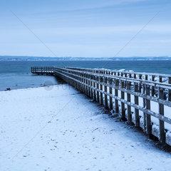 Holzsteg im Schnee an der Ostseekueste