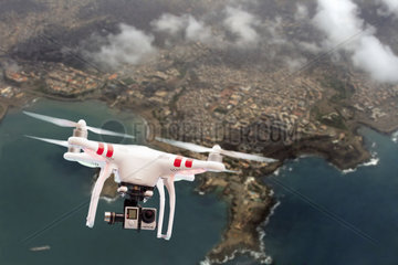 Quadcopter or drone flying over a coastal town