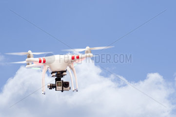 Quadcopter or drone flying against a blue sky with clouds