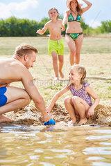 Maedchen baut mit ihrem Vater eine Sandburg