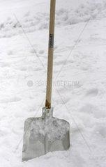 Schneeschaufel steckt im Schnee