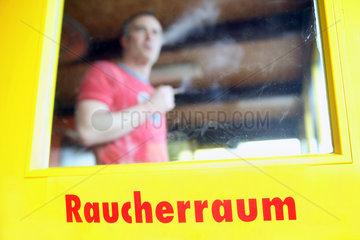 Rostock  Mann in einem Raucherraum im Kinderland Rostock